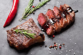 Grilled sliced beef steak with balsamico and rosemary on stone table