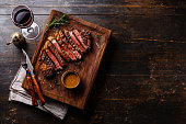 Grilled sliced Steak Rib eye with Pepper sauce and Red wine on wooden background copy space