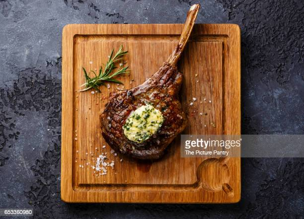 Grilled Steak on bone Veal rib with herb butter on cutting board on dark background