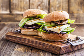 Grilled vegetable and haloumi burger with romaine lettuce on wooden table
