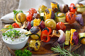 Grilled skewers with mixed vegetables served  on a wooden cutting board with a vegan herb dip