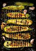 Grilled zucchini with addition of thyme, lemon zest and garlic