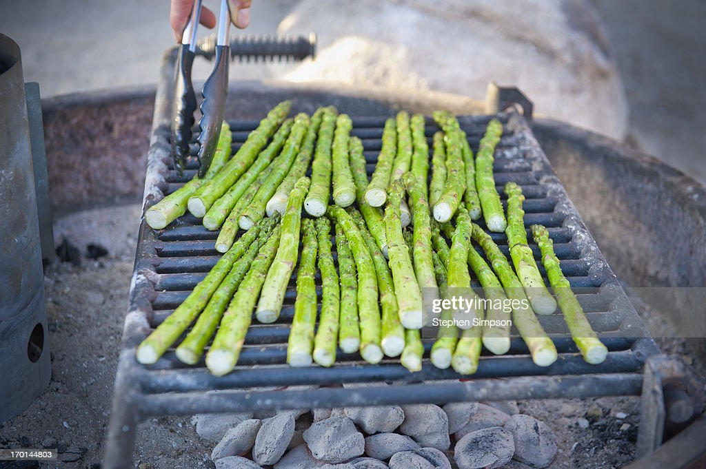 grilling asparagus outdoors over charcoal : Stock Photo