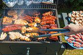 Grilling food on barbecue grill, hands preparing skewers