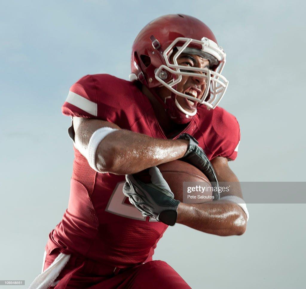Grimacing Black football player carrying football : Stock Photo