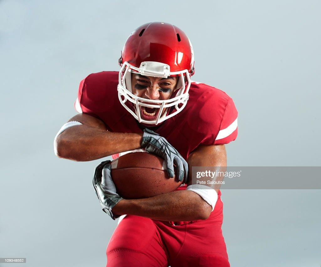 Grimacing Black football player carrying football
