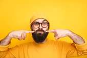 Handsome bearded man in hat and glasses puffing and blowing off cheeks making faces.
