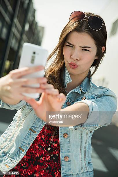Grimacing young woman taking a selfie outdoors