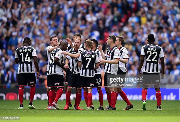 Grimsby Town players commiserate JonPaul Pittman of Grimsby Town after missing his penalty during the Vanarama Conference Playoff Final match between...