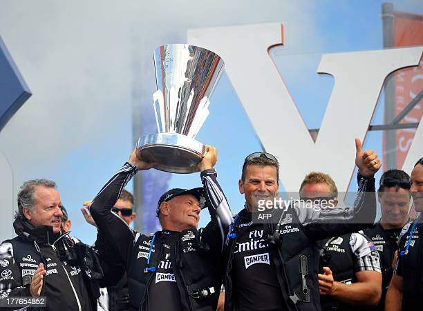 Grinder Grant Dalton holds up the Louis Vuitton Cup while Skipper Dean Barker gives a thumbs up to a cheering crowd during celebrations after...