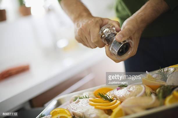 Grinding pepper on rosemary chicken