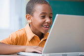 Grinning African boy typing on laptop
