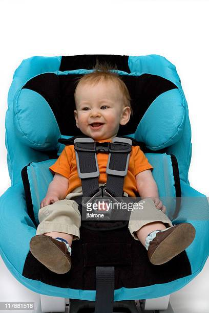 Grinning baby boy sitting in blue and black covered car seat