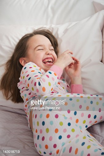 Grinning Caucasian girl laying in bed : Stock Photo