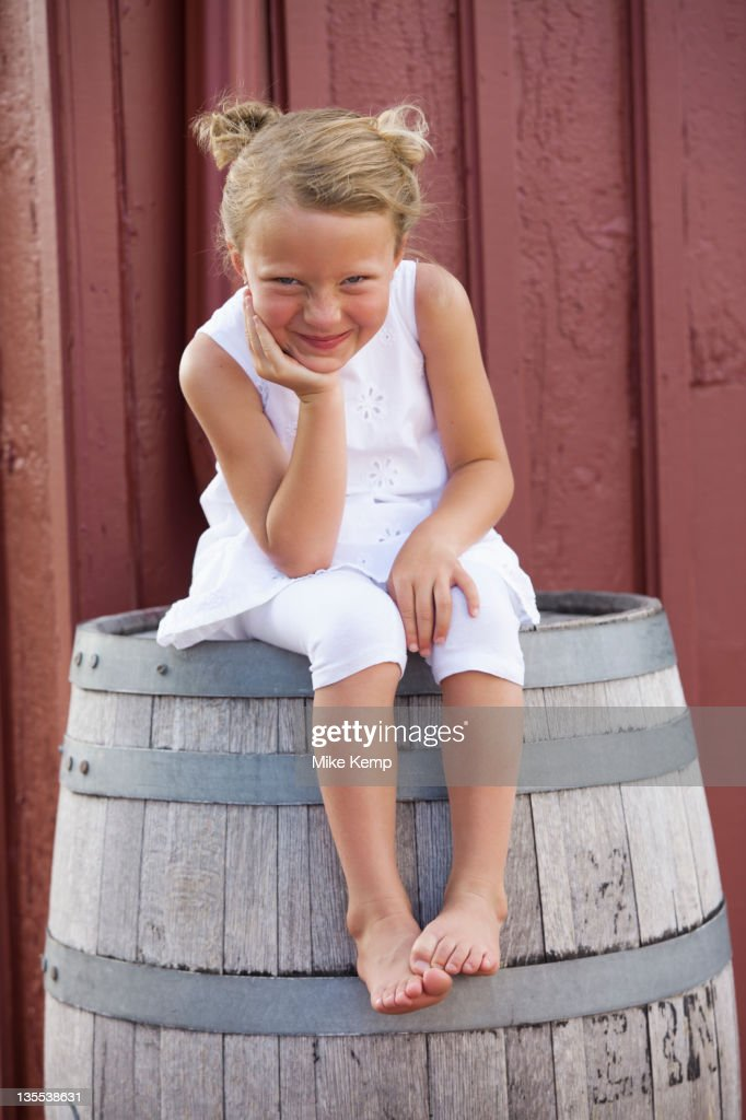 Grinning Caucasian girl sitting on barrel : Stock Photo