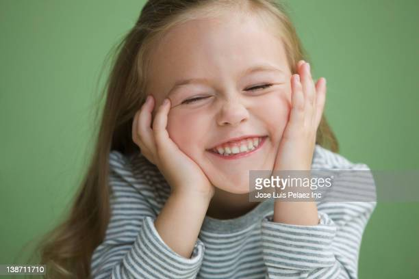 Grinning Caucasian girl with head in hands