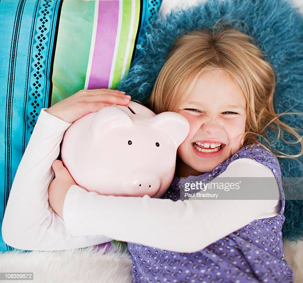 Grinning girl laying in bed with piggy bank