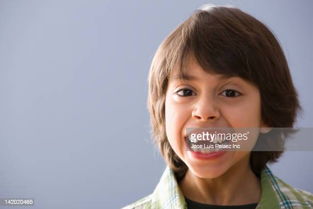 Grinning Hispanic boy with teeth missing