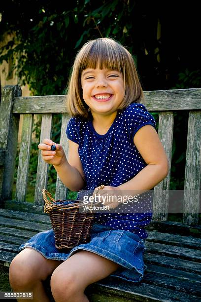 Grinning little girl sitting on a garden bench with wickerbasket of blueberries