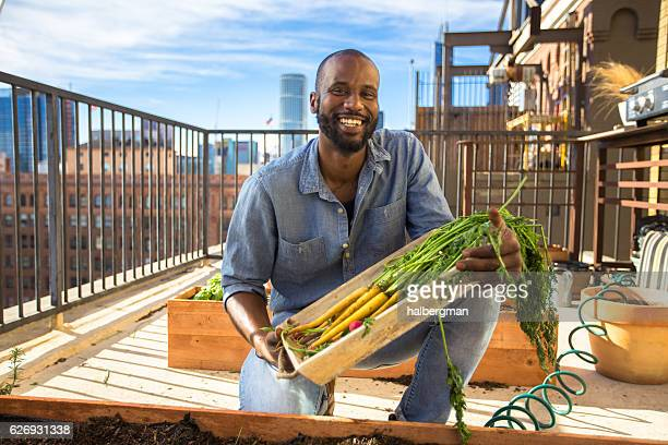 Grinning Man With Urban Rooftop Garden Harvest