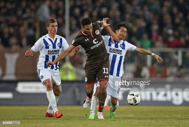Grischa Proemel of Karlsruhe and Aziz Bouhaddouz of Pauli and Hiroki Yamada of Karlsruhe battle for the ball during the Second Bundesliga match...