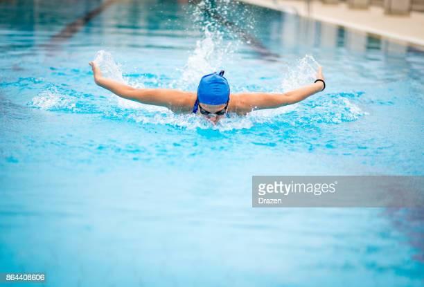 Gritty woman swimming butterfly stroke