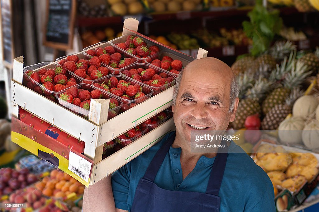 Grocer carrying a box of strawberries : Stock Photo