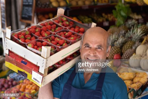 Grocer carrying a box of strawberries