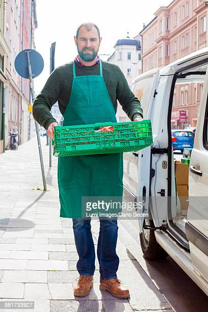 Grocer carrying food in crate by greengrocers shop
