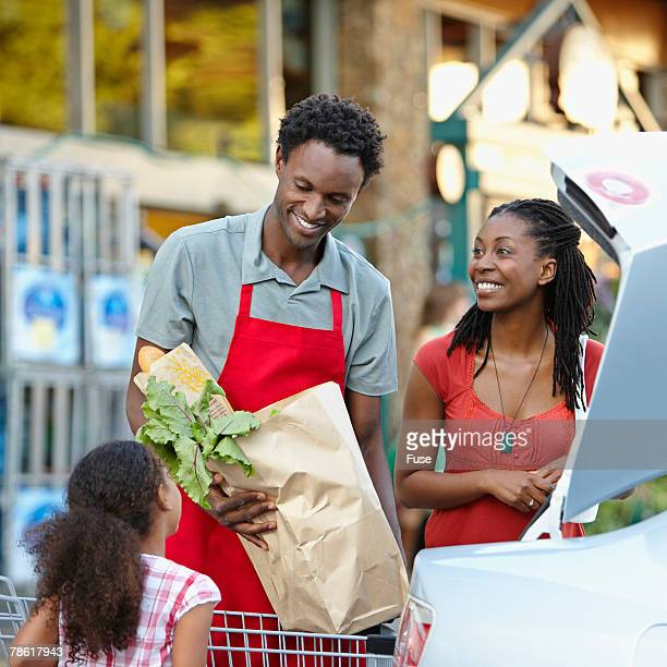 Grocer Helping Mother and Daughter to Car with Groceries