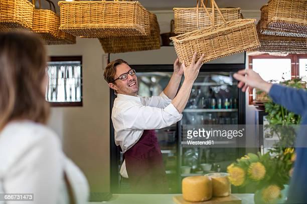 Grocer presenting wickerbasket in a farm shop
