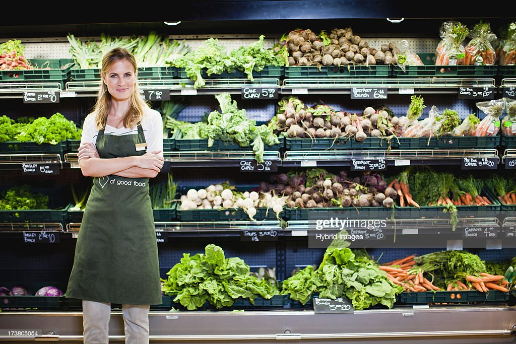 Grocer smiling in produce section : Stock Photo