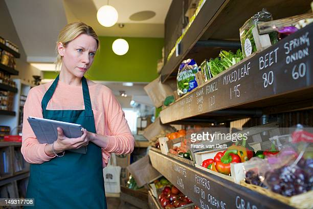 Grocer using tablet computer in store