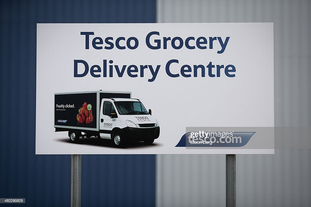A grocery delivery sign stands outside a Tesco Plc on-line distribution center, in Erith, U.K., on Wednesday, Nov. 27, 2013. Tesco Plc, the U.K.'s largest retailer, will sell land near some of its Polish hypermarkets to attract additional services around those stores. Photographer: Simon Dawson/Bloomberg via Getty Images