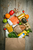 Grocery shopping concept. Balanced diet concept. Fresh foods with shopping bag on rustic wood background, top view, copy space, flat lay