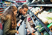 Little girl is buying groceries in the supermarket with her father.
