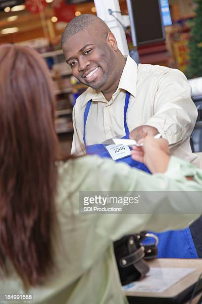 Grocery store checkout worker handing receipt to purchasing customer