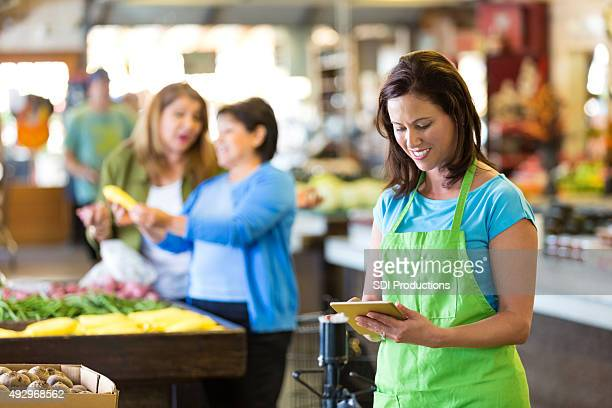 Grocery store employee using digital tablet in produce section
