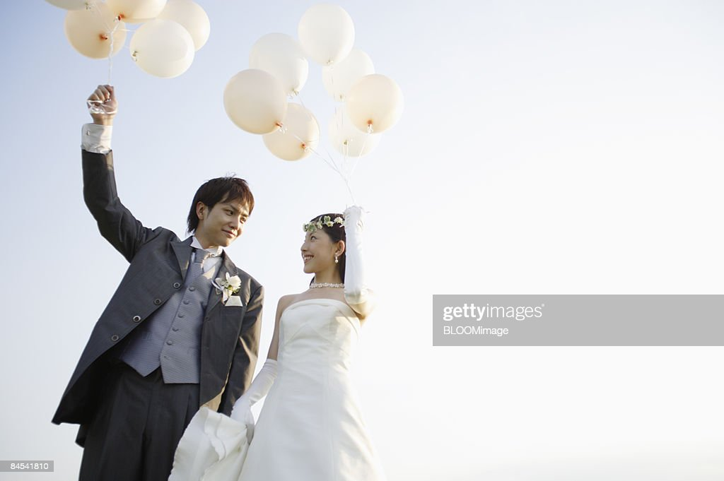 Groom and bride holding balloons : Stock Photo