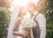 Groom and bride together. Wedding couple kiss and hug each other. focus on Flower bouquet
