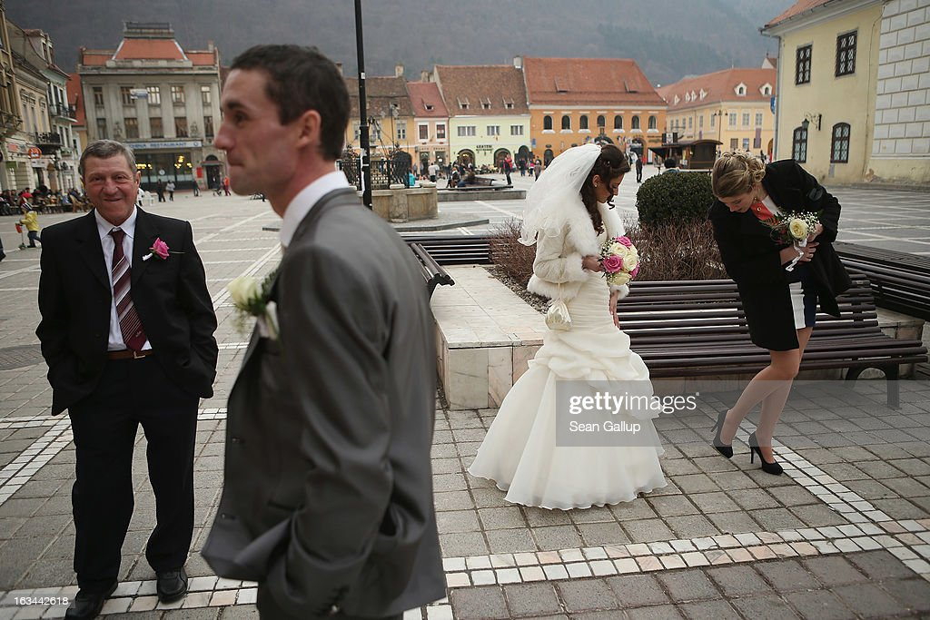 A groom (2nd from L) and bride wait for their Eastern Orthodox church wedding on the Saxon old town square on March 9, 2013 in Brasov, Romania. Both Romania and Bulgaria have been members of the European Union since 2007 and restrictions on their citizens' right to work within the EU are scheduled to end by the end of this year. However Germany's interior minister announced recently that he would veto the two countries' entry into the Schengen Agreement, which would not affect labour rights but would prevent passport-free travel.