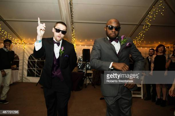 Groom and groomsman dancing at reception