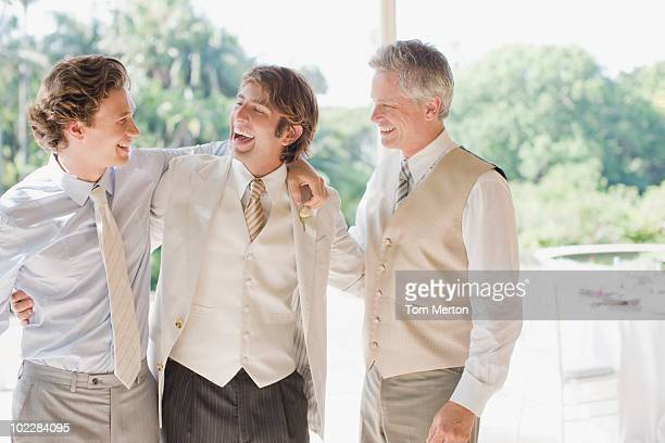 Groom and groomsmen hugging