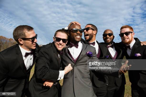 Groom and groomsmen posing for wedding pictures