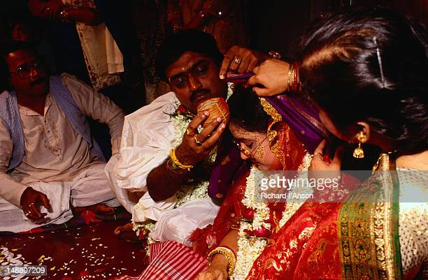 A groom applies red powder between the part in his bride's hair during their wedding ceremony.