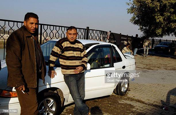 Groom Bashar and a friend wash their cars along the Tigris River in preparation for the honeymoon convoy as the family of Karima Selman Methboub...