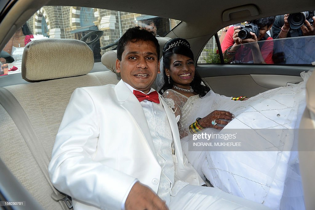 Groom Brandon Pereira (L) and his bride Emilia D'Silva pose after their marriage at the Mount Mary church in Mumbai on December 12, 2012. Couples may be rushing down the aisle on 12/12/12 today in hope of an auspicious union, but Brandon Pereira and Emilia D'Silva can claim an even rarer set of special dates. Brandon Pereira and Emilia D'Silva who have known each other for over 10 years now celebrated their engagement on 10/10/10, had a registered legal marriage on 11/11/11 and finally had their big white wedding in Mumbai on 12/12/12.