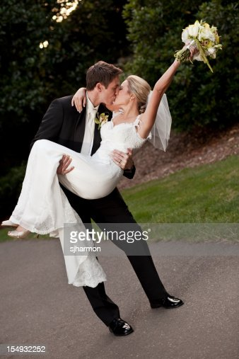 Groom carring Bride kissing park path wearing wedding gown tux