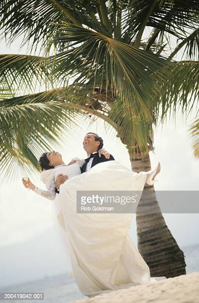 Groom carrying bride in arms at beach