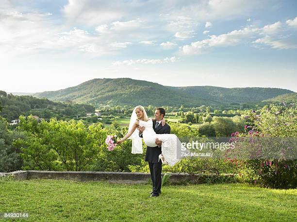 Groom carrying bride in garden